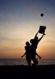Men playing beach ball sport. Men playing beach ball during sunset - Silhouette Royalty Free Stock Photo