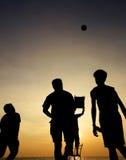 Men playing beach ball sport. Men playing beach ball during sunset - silhouette Stock Photography