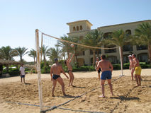 Men playing beach volleyball Stock Images