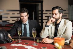 Men playing cards in a casino. Pair of men looking serious while drinking champagne and playing cards in a casino Stock Photos