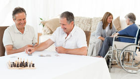 Men playing cards while their wifes are talking Stock Photos