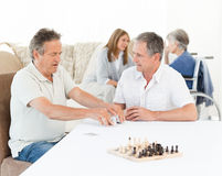 Men playing cards while their wifes are talking Royalty Free Stock Photo