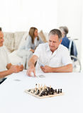 Men playing cards while their wifes are talking Royalty Free Stock Photography