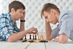 Men playing chess at home Stock Images