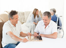 Men playing chess while their wifes are talking Royalty Free Stock Images