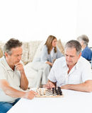 Men playing chess while their wifes are talking Stock Image