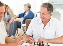 Men playing chess while their wifes are talking Stock Photos