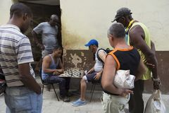 Men playing chess under the watchful eye of other men in Old Havana royalty free stock photo