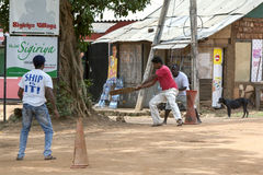 Men playing cricket on a dirt pitch in the street at Sigiriya, Sri Lanka. Stock Photo