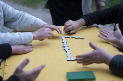 Men playing dominoes at yellow table Royalty Free Stock Photo