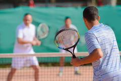 Men playing doubles game tennis Stock Image