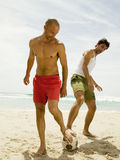 Men playing football on the beach.  Stock Image