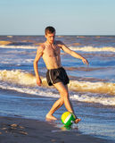 Men playing football on the beach coast. At sunset Royalty Free Stock Photography