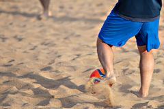 Men playing football on the beach. Red ball.  Stock Photos