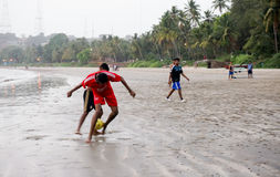 Men playing football (soccer) on goa beach. Goa, India; 7th April 2015: Men competing for a football (soccer) on Bambolim beach in Goa. This is a popular Stock Image