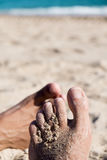 Men playing footsie on the beach Stock Image