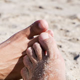 Men playing footsie on the beach Royalty Free Stock Photo