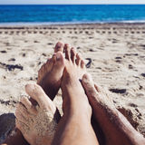Men playing footsie on the beach Royalty Free Stock Photos
