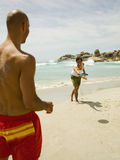 Men playing frisbee on the beach. Men playing frisbee on the beach, in front of the sea Stock Image