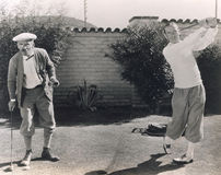 Men playing golf in backyard royalty free stock images