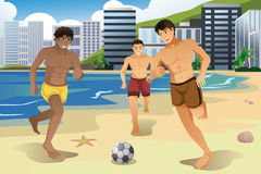 Men playing soccer on the beach Stock Images
