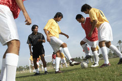 Men Playing Soccer While Referee Watching Them. Low angle view of young men playing soccer while referee watching them on field Stock Image