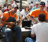 Men playing stringed instruments at festival Stock Photography