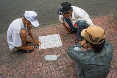Men playing traditional board game in Saigon, Vietnam. Royalty Free Stock Images
