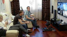 Men playing video game and girl using cell phone. Two men sitting on the sofa at home and playing video game with gamepads, while girl using smartphone stock video