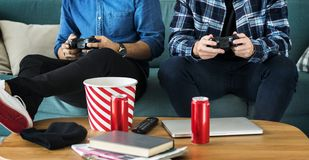 Men playing video game on a sofa leisure and teamwork concept Royalty Free Stock Photo
