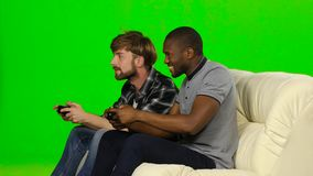 Men playing video games against each other. Green screen stock video