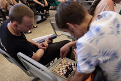 Men plays chess in a waiting hall Royalty Free Stock Photography