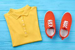 Men polo t-shirt, shoes. Men polo t-shirt, hoes. Set of bright summer clothing, wooden background Royalty Free Stock Images