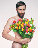 Men portrait with a bouquet of flowers. Studio photo middle-aged man with a bouquet of tulips Stock Images