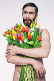 Men portrait with a bouquet of flowers. Studio photo middle-aged man with a bouquet of tulips Stock Photography