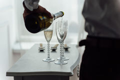 Men pour champagne into glasses. From wine bottles. To celebrate a successful deal Royalty Free Stock Photography