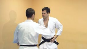 Men practicing Aikido in gym with wooden knives. Athletes with wooden knives demonstrating martial arts techniques stock video