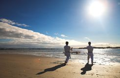 Men practicing Karate on beach royalty free stock photos
