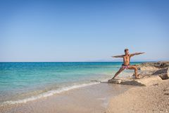 Men practicing yoga on the beach in Greece, in position wa. Adult man practicing yoga on the beach in Greece, in position warrior two Stock Photos