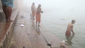 Men praying and bathing on shore of foggy Ganges river in Varanasi. VARANASI, INDIA - 19 FEBRUARY 2015: Men praying and bathing on shore of foggy Ganges river stock footage