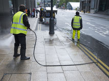 Men with pressure washer clean the satreets of canary wharf in l Royalty Free Stock Photos