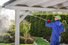 Free Men Pressure Washing Garden Porch Wooden Roof Royalty Free Stock Images - 189536279