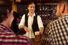 Men in pub. Attractive bartender is smiling and offering a glass of beer to men sitting at bar counter in pub Royalty Free Stock Photos