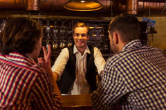 Men in pub. Attractive bartender is smiling and taking order of two men sitting at bar counter in pub Stock Photos