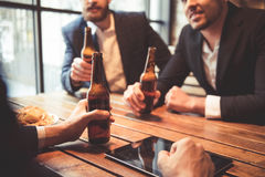 Men at the pub. Handsome businessmen are drinking beer, talking and smiling while resting at the pub stock images