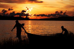 Men push the boat. To the shore at sunset Stock Photography