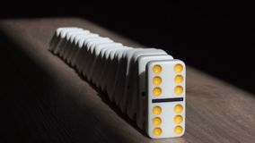 Men pushes a Domino and starts a chain reaction on floor in a patch of sunlight.