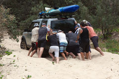 Men pushing bogged car Royalty Free Stock Photography