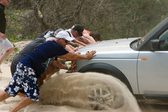 Men pushing bogged car Royalty Free Stock Photography