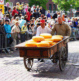 Men pushing cheese on a cart Royalty Free Stock Photography